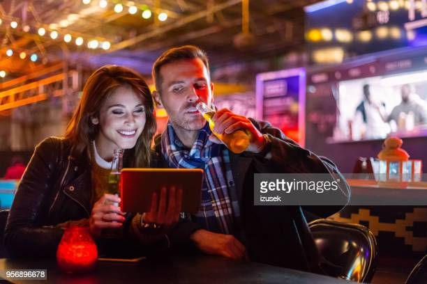 couple sitting together in a pub in the evening, using digital tablet - izusek stock pictures, royalty-free photos & images