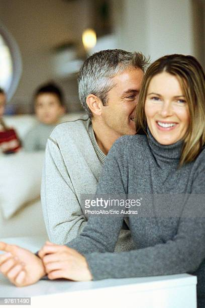Couple sitting together, man whispering in woman's ear