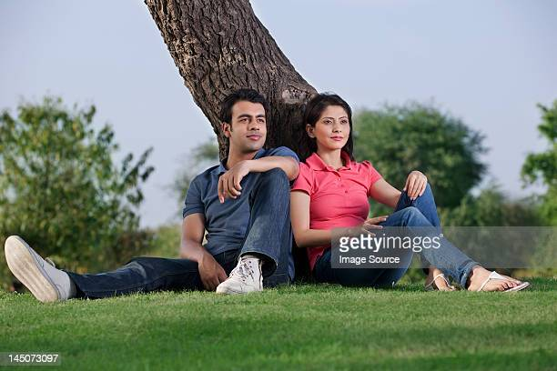 Couple sitting together next to a tree