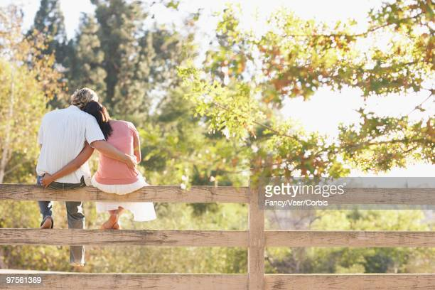 Couple Sitting Together on a Fence