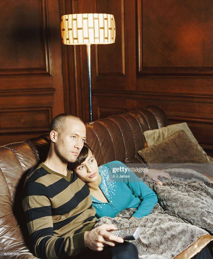 Couple Sitting Together on a Sofa and Watching TV : Stock Photo