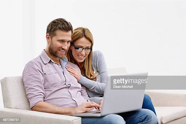 Couple sitting together on a sofa using laptop