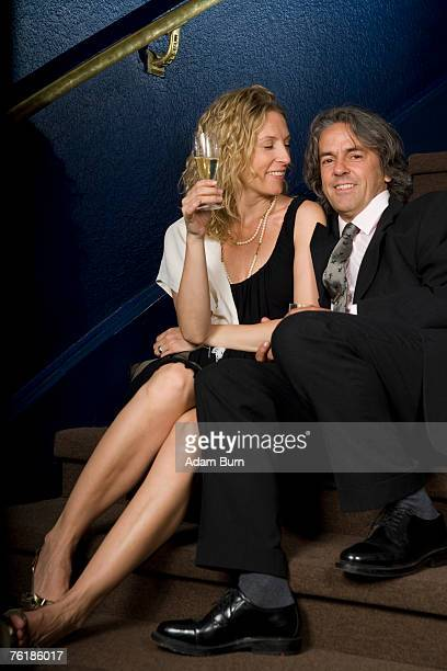 A couple sitting together on a staircase in a theater