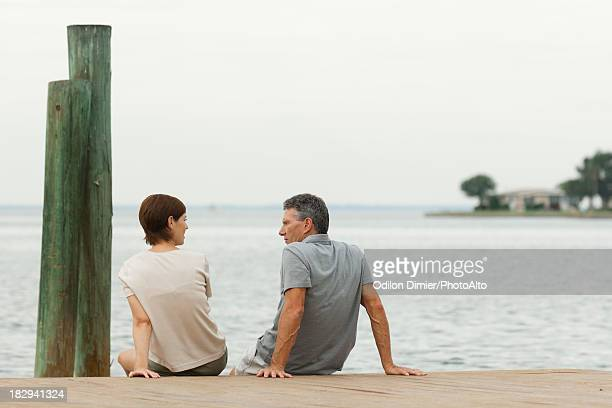 Couple sitting together on dock, rear view