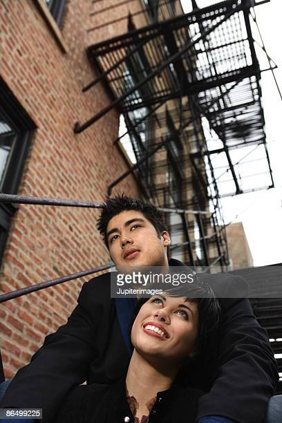 Couple sitting together on fire escape