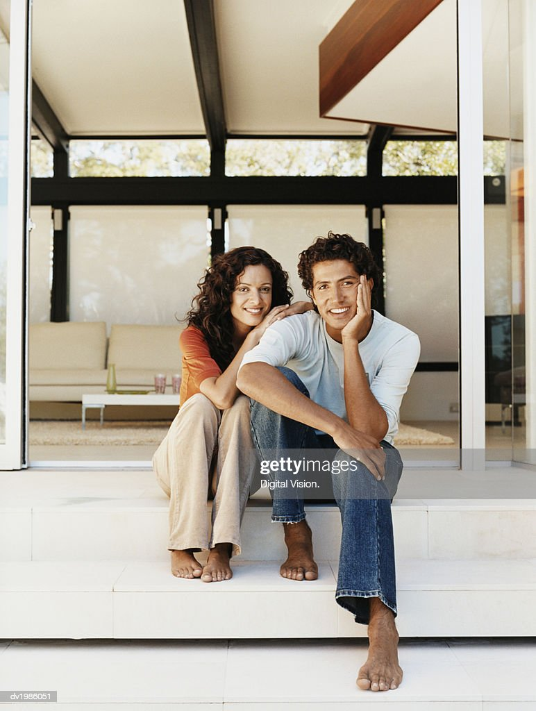 Couple Sitting Together on Steps by a Patio Door : Stock Photo
