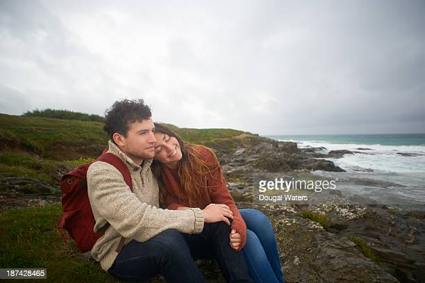 couple sitting together on uk coastline. - dougal waters stock pictures, royalty-free photos & images