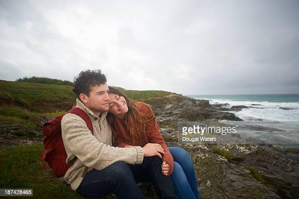 Couple sitting together on UK coastline.