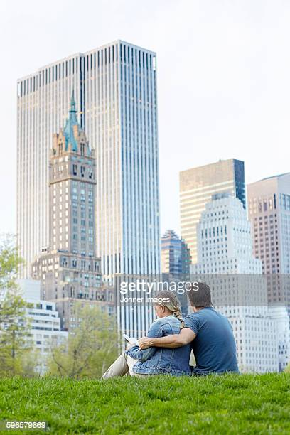Couple sitting together, skyscrapers on background