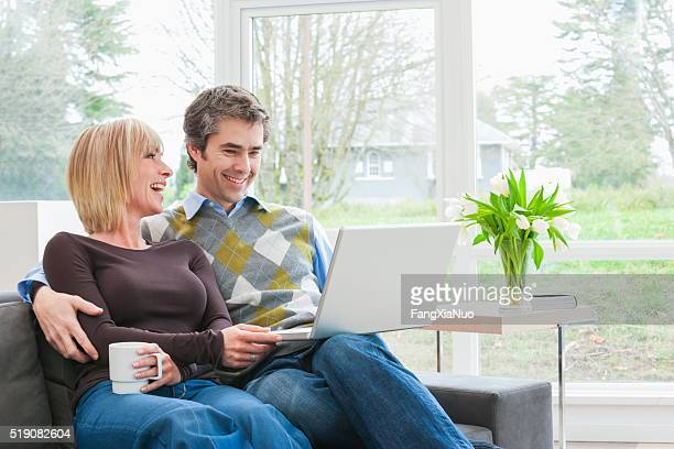 Couple sitting together using laptop