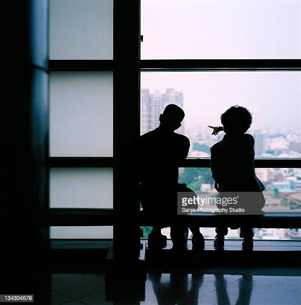 couple sitting together watching city view - studio city stock pictures, royalty-free photos & images
