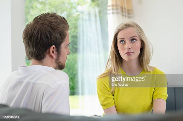 Couple sitting together, woman ignoring boyfriend