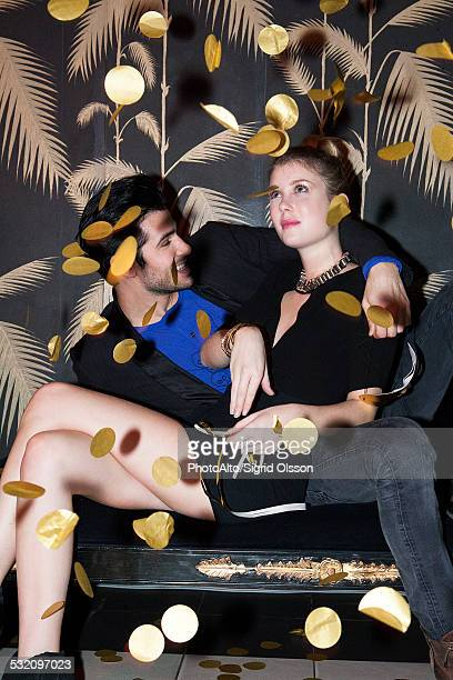 Couple sitting under falling confetti at party