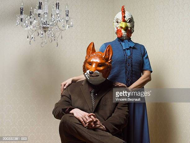 Couple sitting wearing fox and chicken masks, portrait