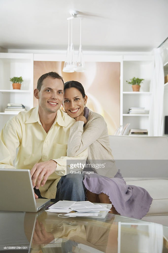Couple sitting with laptop, smiling, portrait : Stockfoto