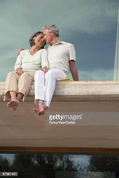 Couple sitting with legs dangling over ledge