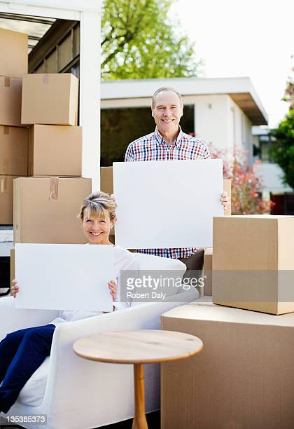 Couple sitting with moving boxes holding blank cards
