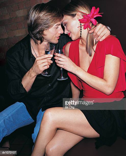 couple sitting with their arms around each other and holding champagne flutes - clubkleding stockfoto's en -beelden