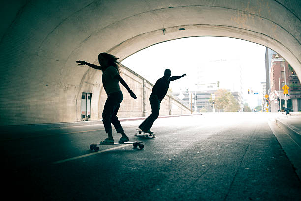 Couple skateboarding through tunnel