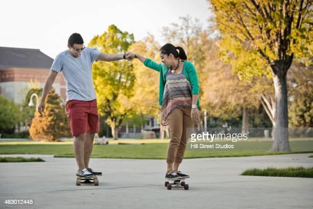 couple skateboarding together in park - caldwell idaho foto e immagini stock