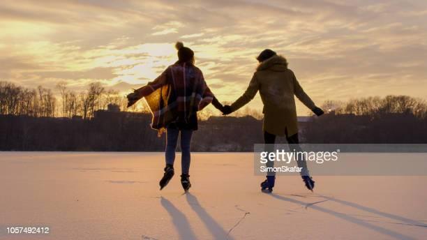 pareja patinando en el lago congelado - patinar fotografías e imágenes de stock