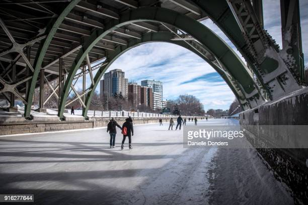 Couple skating on Rideau Canal under the bridge and holding hands during Winterlude