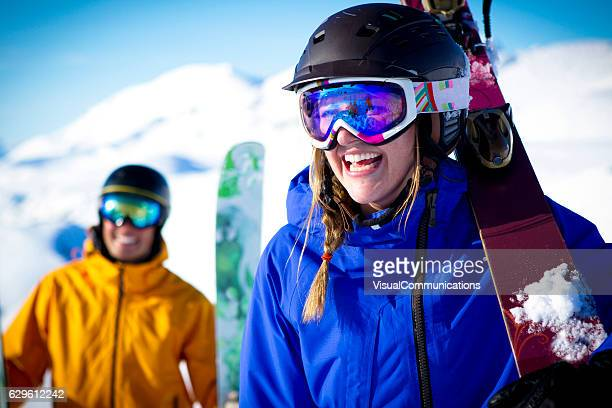 Couple skiers smiling in mountains.