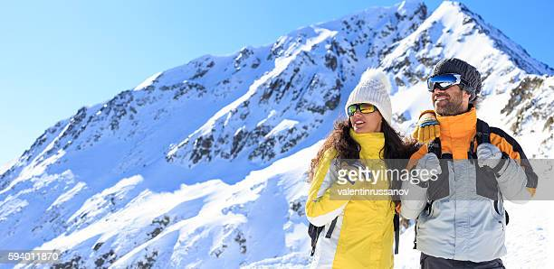 Couple skiers standing on top of the mountain