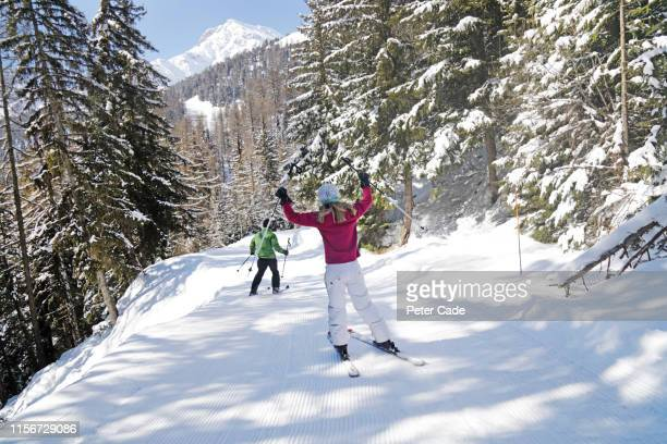couple skiing down mountain - skiing stock pictures, royalty-free photos & images