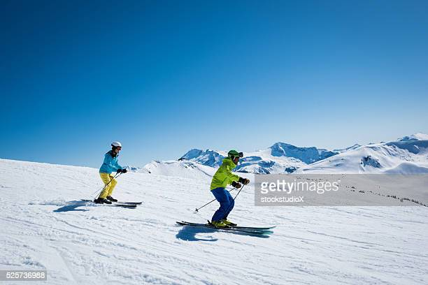 couple skiing on a sunny day - whistler british columbia stock pictures, royalty-free photos & images