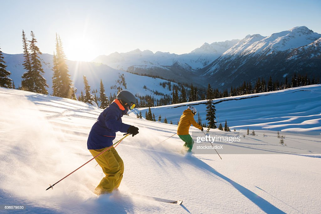Couple skiing on a sunny powder day : Stock Photo