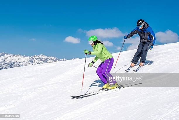 couple skiing on mountain slope - ski holiday stock photos and pictures