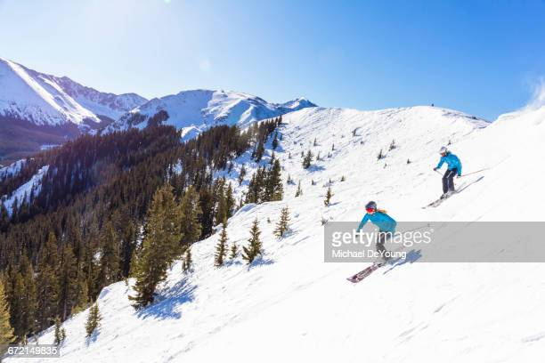 couple skiing on snowy mountain slope - women in sheer clothes stock photos and pictures