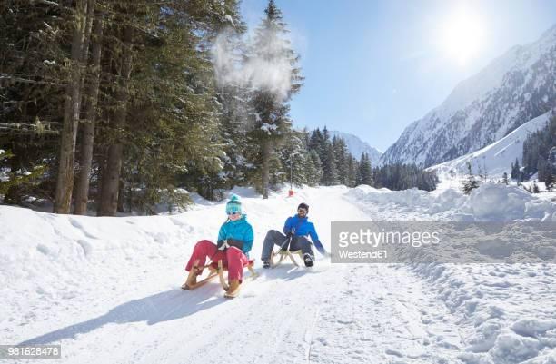 couple sledding in snow-covered landscape - schlitten stock-fotos und bilder