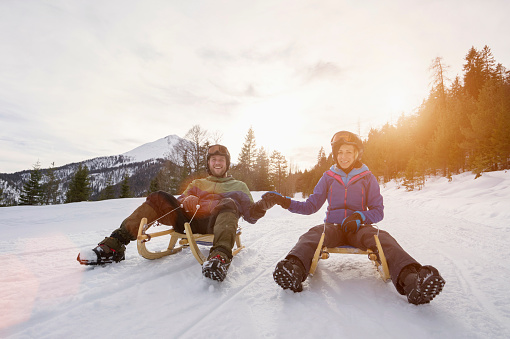 Couple sledding on winter landscape - gettyimageskorea