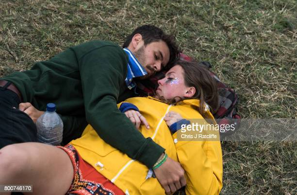 A couple sleep next to each other during the afternoon at the Pyramid Stage at Glastonbury Festival Site on June 25 2017 in Glastonbury England As...