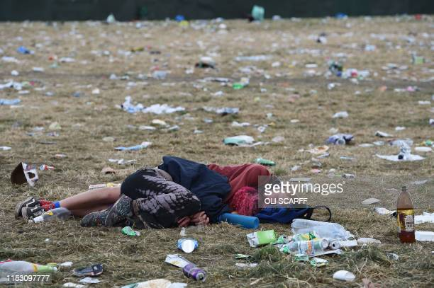 A couple sleep on the ground in front of the pyramid stage at Glastonbury Festival of Music and Performing Arts on Worthy Farm near the village of...