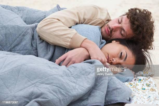 Couple sleep on the sand at Bondi Beach on January 01, 2020 in Sydney, Australia. New Years's Eve celebrations went ahead in Sydney despite...