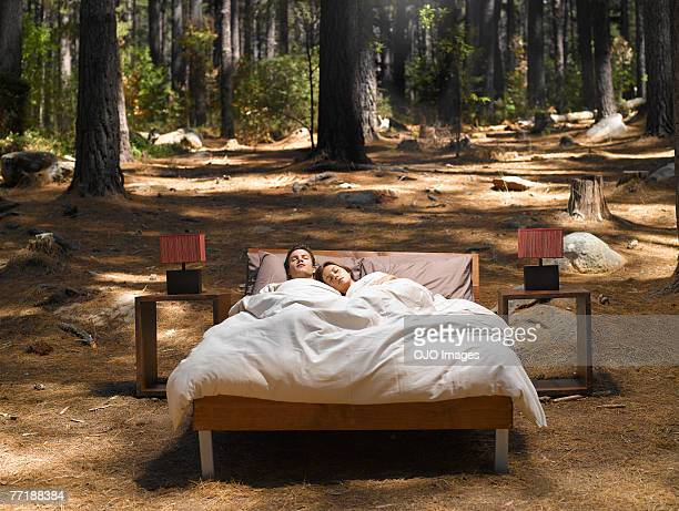 a couple sleeping in a bed outdoors in the woods - freaky couples stock photos and pictures