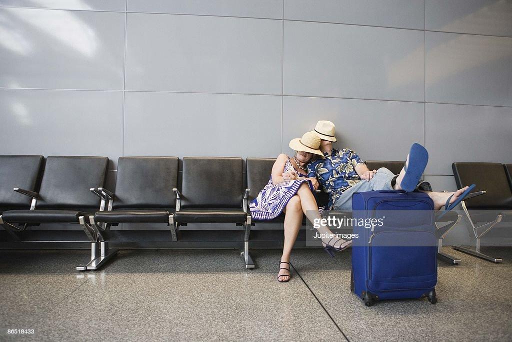 Couple sleeping in airport : Stock Photo