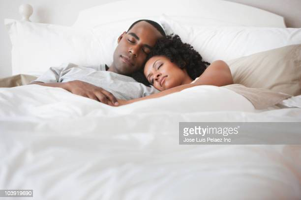 couple sleeping in bed - couple sleeping stock pictures, royalty-free photos & images