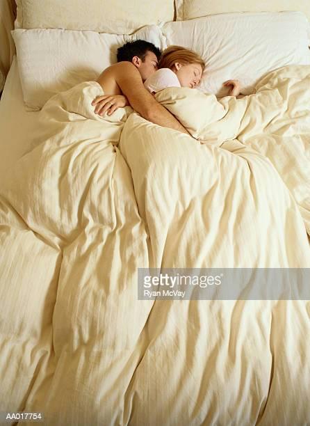 couple sleeping in bed - abbracciarsi a letto foto e immagini stock