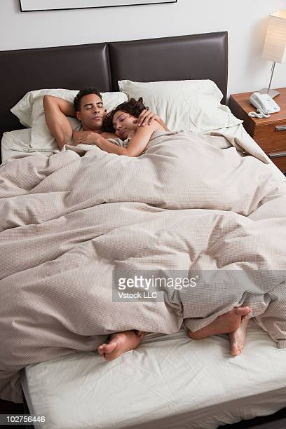 couple sleeping in bed together - black man sleeping in bed stock pictures, royalty-free photos & images