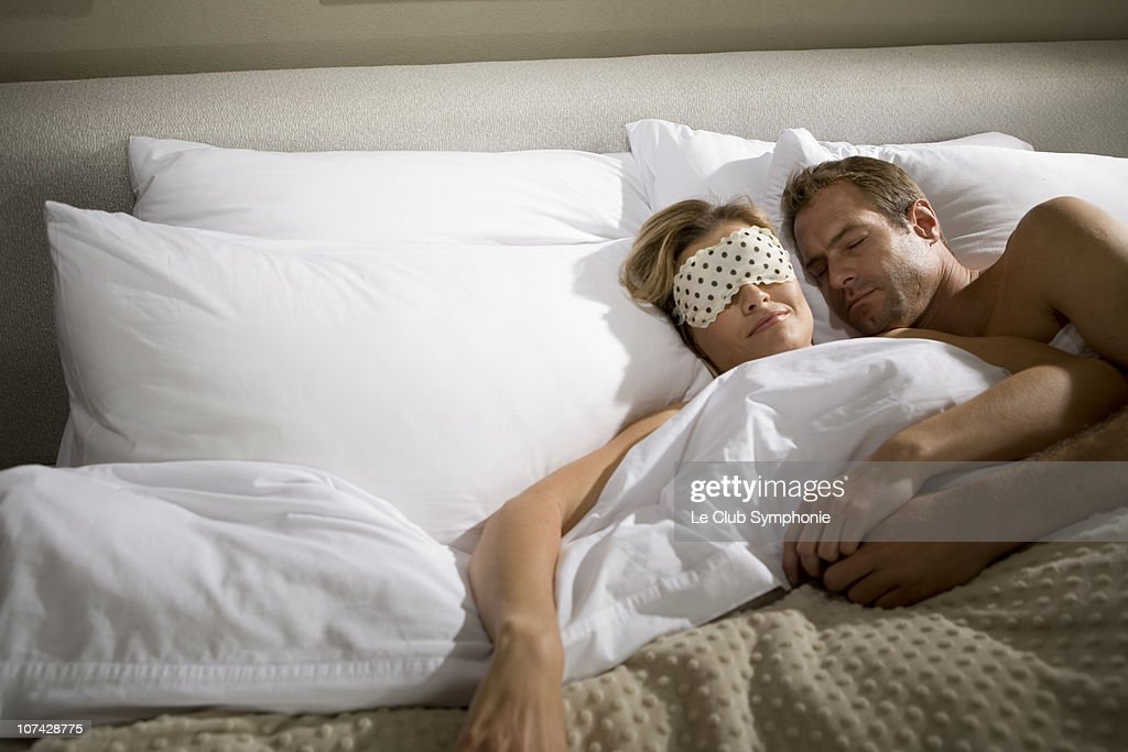 Couple sleeping in bed together : Stock Photo