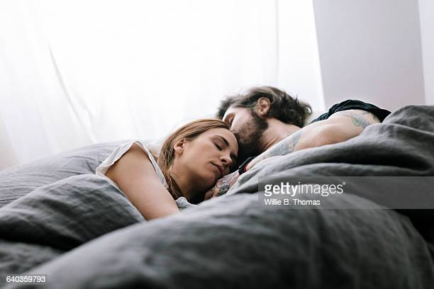 couple sleeping in bed together - koppel stockfoto's en -beelden