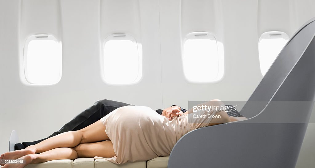 couple sleeping in reclining chair on airplane stock photo