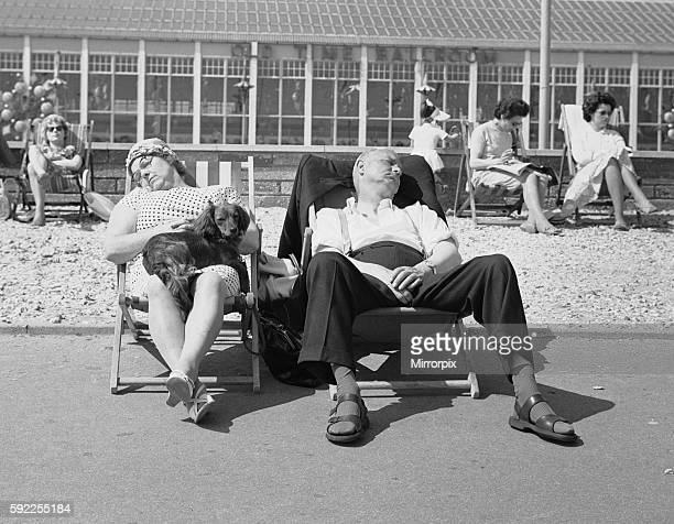 Couple sleeping in their deckchairs with their dog on the promenade at Bognor Regis 10th June 1962.
