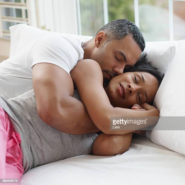 couple sleeping on bed - black man sleeping in bed stock pictures, royalty-free photos & images