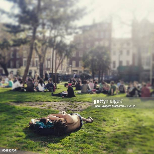 Couple Sleeping On Grass At Park