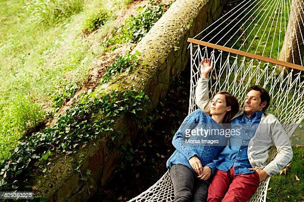 Couple sleeping on hammock at park